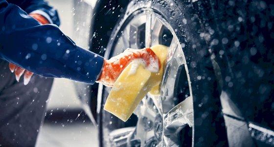 Person poliert die Felgen eines Volvo mit einem gelben Schwamm
