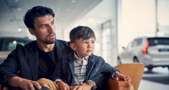 Ein Mann sitzt mit seinem Kind in einem Autohaus, mehrer Volvo-Fahrzeuge im Hintergrund