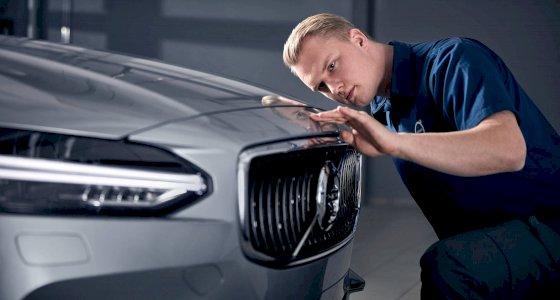 Mechaniker begutachtet die Front eines Volvo in einer Werkstatt