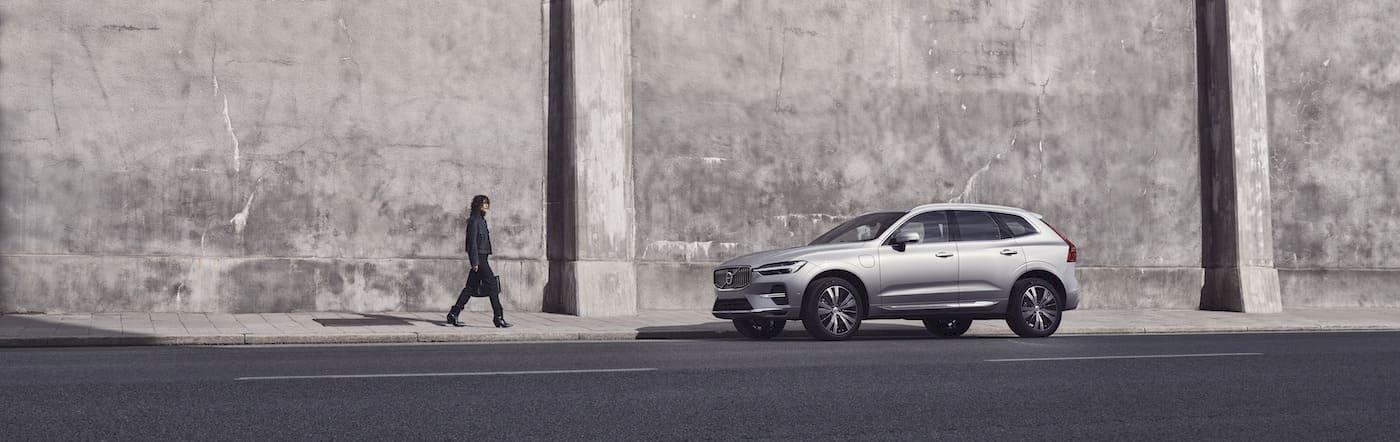 Frau geht auf Volvo XC60 Plug-in Hybrid zu