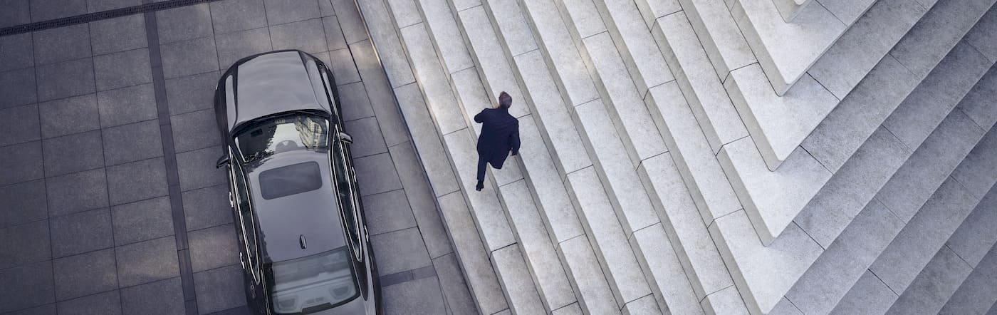 Mann geht auf Treppe von einem Volvo S90 weg